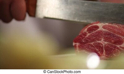 Mans hand cut fresh meat by big knife Restaurant Close up...