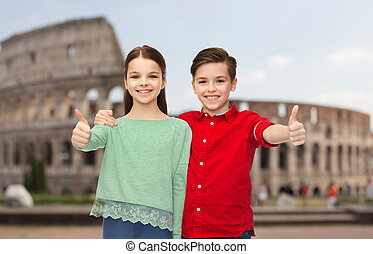 happy boy and girl showing thumbs up over coliseum
