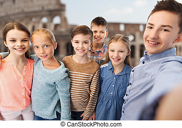 children talking selfie over coliseum in rome - childhood,...