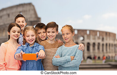 children talking smartphone selfie over coliseum -...