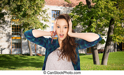 pretty teenage student girl holding to head - people,...