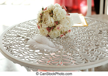 Beautiful elegant and stylish feather, rose bouquet on white table