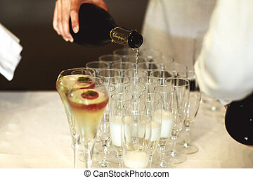Elegant waiter pouring champagne in glasses at wedding...