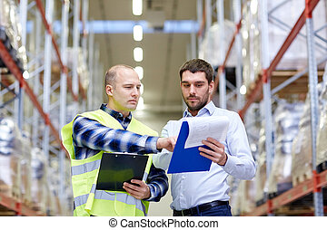 worker and businessmen with clipboard at warehouse -...