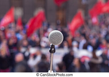 Public demonstration. Protest. - Microphone in focus against...