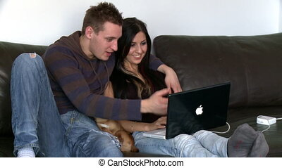 Happy couple looking at a laptop sitting on sofa at home