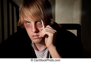 Depressed young man smoking in a tenement hovel