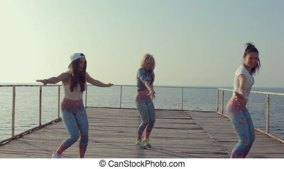 Young girls dancing modern dance on the pier near sea