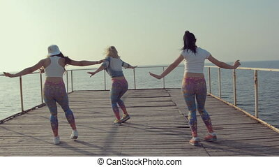 Three teenage girls dancing dance hall on the docks near sea
