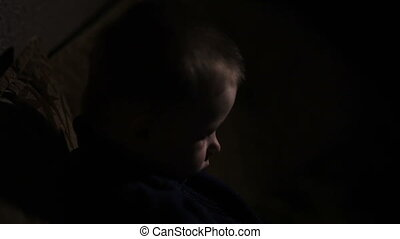 little boy sits on sofa in dark room