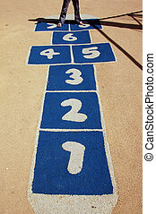 Close up of play hopscotch with white figures on blue...