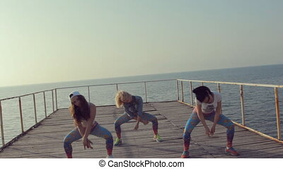 Booty dance by girls teenager on a wooden berth at the sea -...