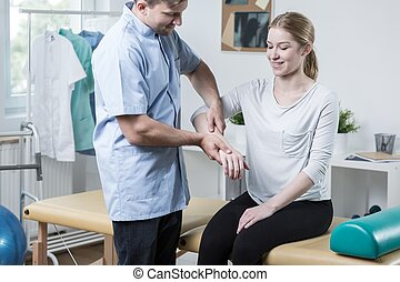 Woman visiting a physiotherapist - Woman with arm injury...