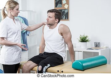 Injured sportsman and young physiotherapist - Injured...