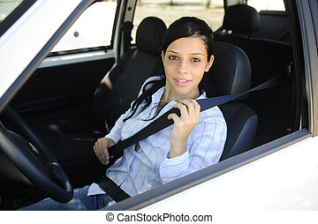 safety: female driver fastening seat belt - car safety:...