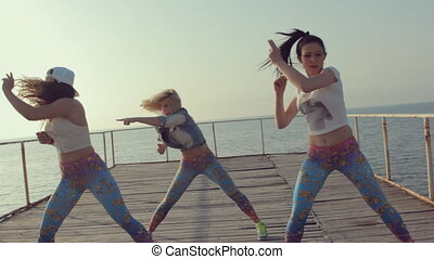 Twerk by young energetic teen girls on a wooden pier near the sea
