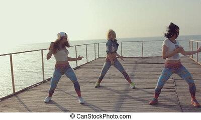 Energetic twerk by trendy teen girls on a wooden pier near the sea