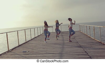 Girls in bright leggings professionally dancing modern dance on a wooden pier near the sea at sunset
