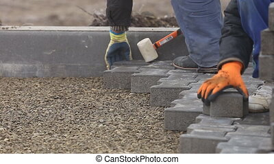 Worker puts sidewalk tile closeup