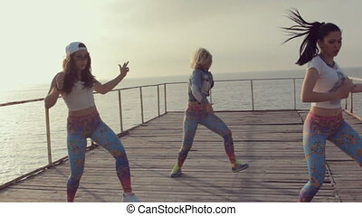 Talented energetic girl dancing twerk in sunset by the sea -...