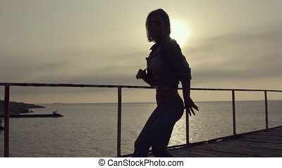 Girl with a sports figure and short hair incendiary dancing booty dance on the pier near the sea at sunset