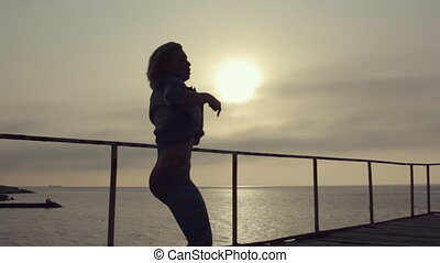 Girl with a sexy figure and short hair incendiary dancing on the pier near the sea at sunset