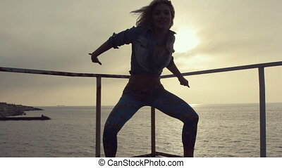 Positive young sexy woman dancing twerk on the pier near the...