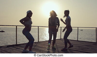 Training in dancing of three girls in same clothes on a pier...