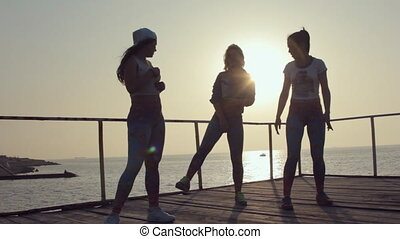 Three talented young girls coming up with dance performance on the pier near the sea at a sunset