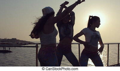 Three cheerful girls dressed in the same leggings dancing at...