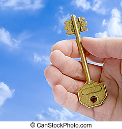 Key To Success - Golden Key In A Hand Against Blue Sky