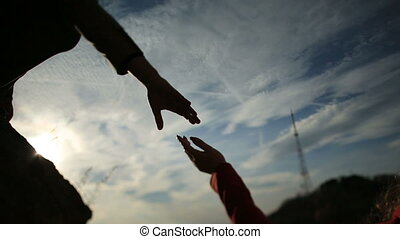 Couple holding hands at sunset silhouetted.