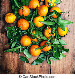 Fresh picked tangerines over wooden background