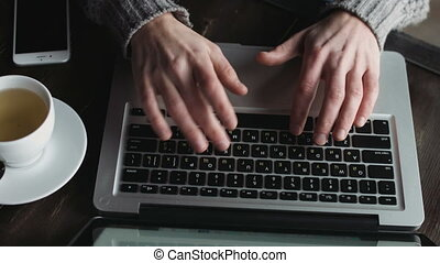 Close-up of young male hands typing on a keyboard inside a cafe