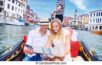 Loving couple traveling to Venice, searching on the map...