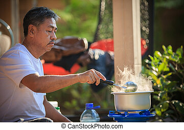 old man cooking morning food meal in hot pot on lpg gas...
