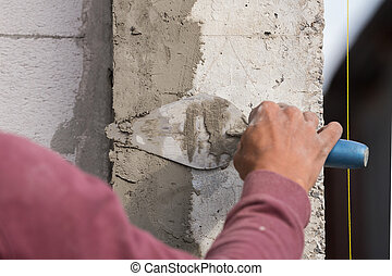 plasterer concrete worker at wall of house construction at...