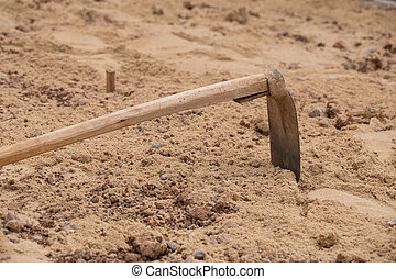 soil with a hoe at construction site