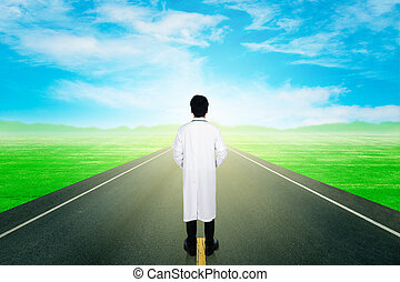 doctor with asphalt road through the field with sky - doctor...