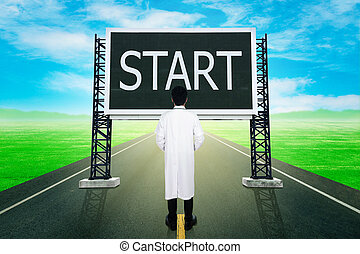 doctor standing on road and looking with large sign of start...