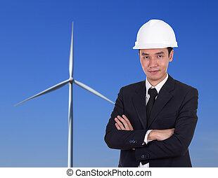 engineer in helmet with arms crossed, wind turbine background