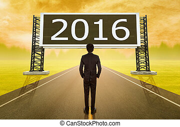 businessman standing on road and looking with large sign of 2016 new year