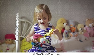 Cute kid girl playing with toy at home