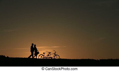 Silhouette of  Beautiful Couple With Tandem Bicycles Walking Against Fabulous Sunset Backgrund Close Up
