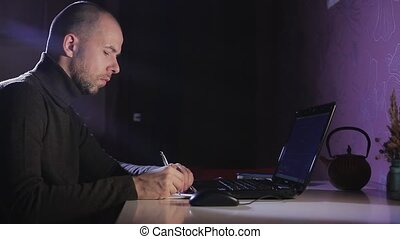 Portrait of a man on his laptop at night with a face of concentration.