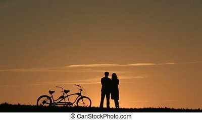 Silhouette of Romantic Couple With Tandem Bicycles Watching...