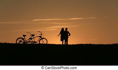Silhouette of Beautiful Couple With Tandem Bicycles Against...