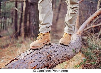 Hiker walking on tree trunk