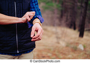 Hiker man rolling his sleeves - Hiker young man rolling his...