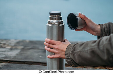 Woman opening a thermos - Unrecognizable woman opening a...